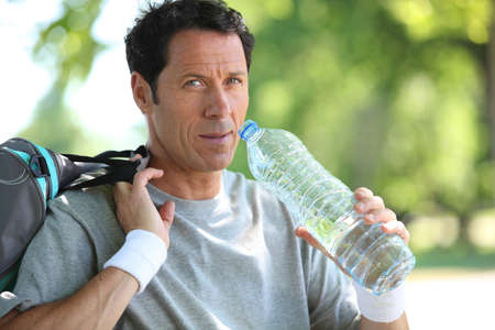 man in sports clothes drinking water photo