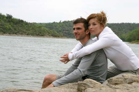 sporty: Couple sat by lake