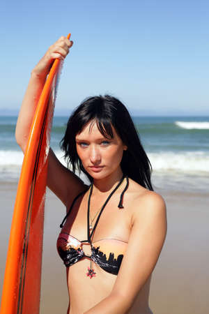 watersports: Young woman with a surfboard