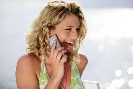 Blond woman making telephone call at the beach photo