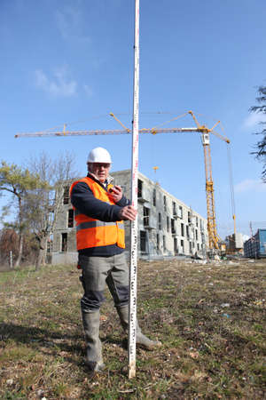 Tradesman holding a measuring stick photo