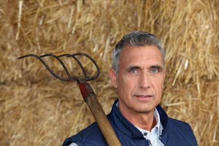 45 50 years: Farmer holding a pitchfork Stock Photo