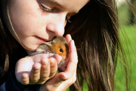 Little girl with her pet hamster photo