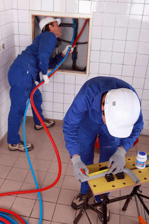 Workers  repairing pipes photo