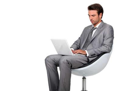 hombre sentado: Hombre joven en traje gris