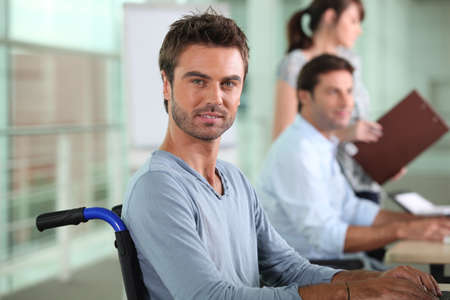 proactive: Man in a wheelchair working in an office Stock Photo