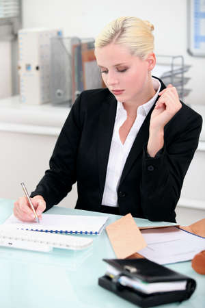 25 30 years old: Young businesswoman writing notes at her desk Stock Photo