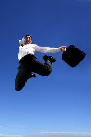 businessman jumping: Businessman with briefcase jumping for joy