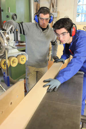 apprentice: Carpenters cutting a plank of wood