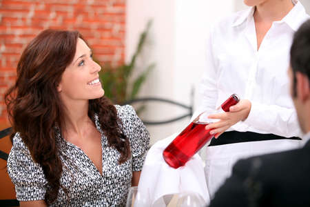 Waitress presenting bottle of wine to couple photo