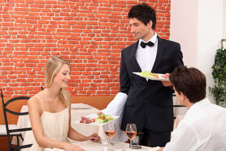 Couple being served their meal photo
