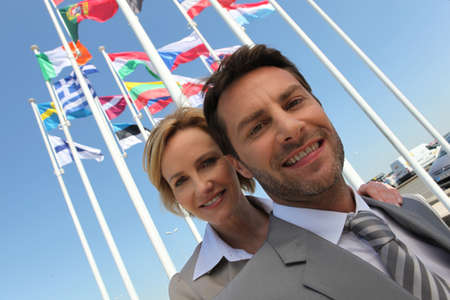 40 45: Businessman and woman with flags.