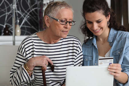 grandma and home helper with laptop photo