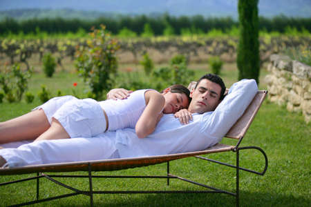 Couple having a nap on sun lounger photo
