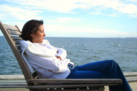 blue sky thinking: Woman sitting in a chair by the waterfont Stock Photo