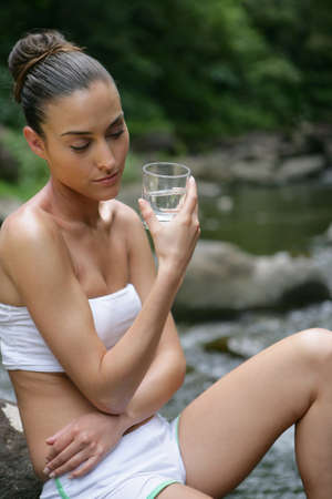 water source: Woman drinking glass of water by the river