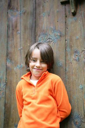 Boy stood by big wooden door photo