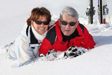 Older couple lying in the snow Stock Photo - 12362581