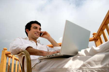 Homme de d�tente avec tout ordinateur portable assis dans le jardin photo