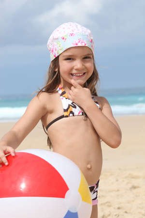 Young girl in a bandana with a beach ball photo