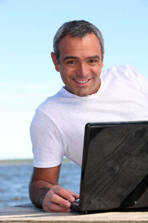 40 years old man: 40 years old man doing computer behind the sea