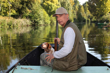 50 54 years: Hunter with a shotgun and dog on a boat