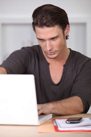 Man looking at his laptop photo