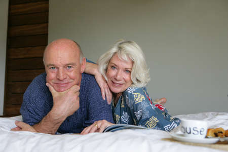 Senior couple enjoying breakfast in bed photo