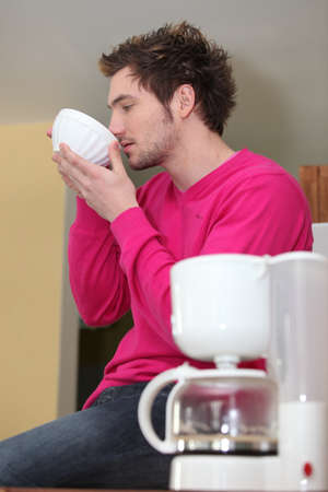 Man drinking coffee out of a bowl