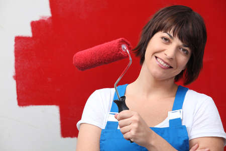 wet t shirt: Woman painting wall red with roller
