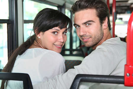 25 to 30: Young couple sitting on a bus