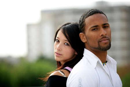 ethnic couple: Teenagers standing back to back