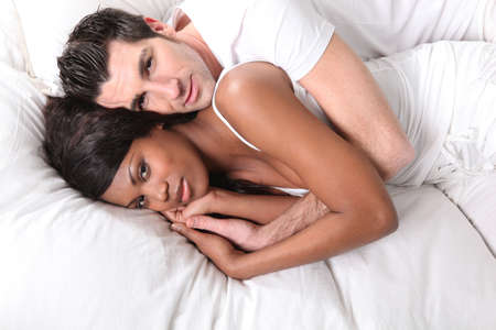 Couple embraced in snug bed photo