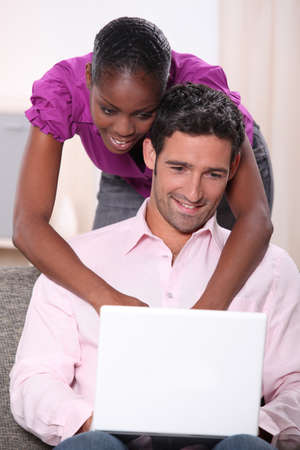 black woman leaning on his boyfriend  and doing computer laid on his boyfriend photo