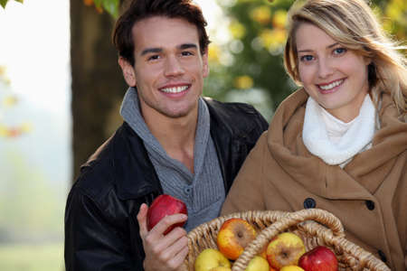 couple gathering apples in the garden photo