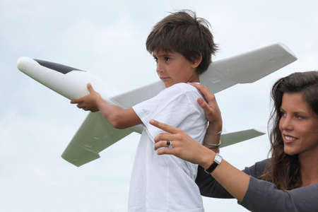 pretend: Mother and son playing with a large model toy aeroplane