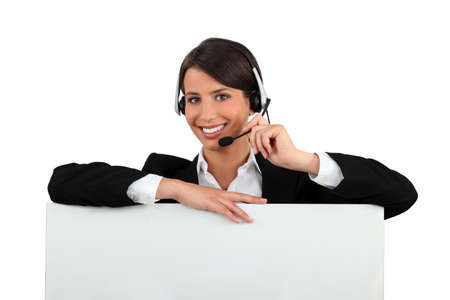 Woman with a headset and a board left blank for your message Stock Photo - 12362440