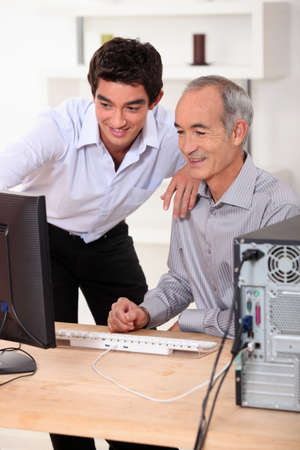 Younger and older men looking at a computer photo