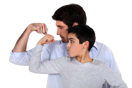30 to 35: Father and son comparing their muscles Stock Photo