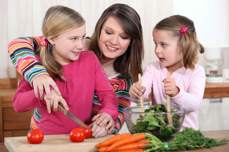 Mother chopping vegetables with two daughters photo