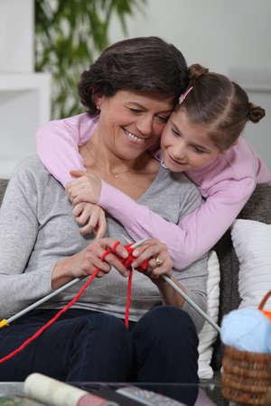 fond of children: Grandma knitting with her grandchild