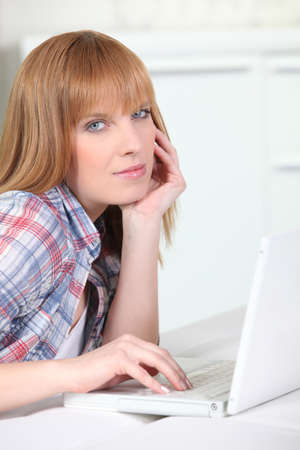 causal: Causal redheaded woman using a white laptop computer