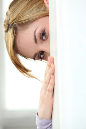 glimpse: Woman hiding behind wall
