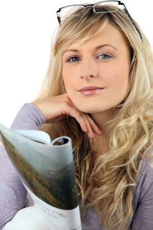 Blond woman reading magazine photo