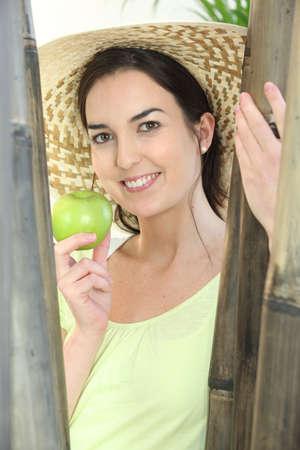 boast: Donna che porta il cappello e che tiene mela verde