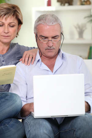 Middle-aged couple sat on sofa with laptop and book photo