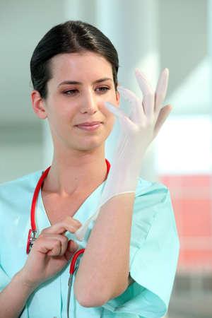 examenes de laboratorio: mujer médico de ponerse los guantes de goma