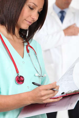 Nurse in scrubs with a clipboard Stock Photo - 12366053