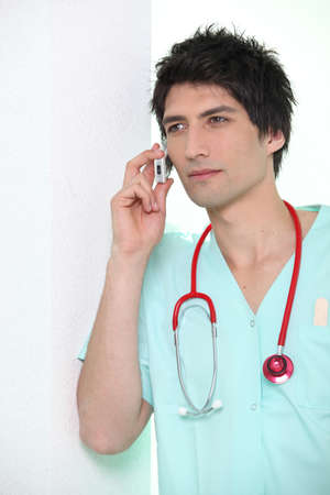 Male nurse leaning against wall holding  mobile telephone to ear Stock Photo - 12376111