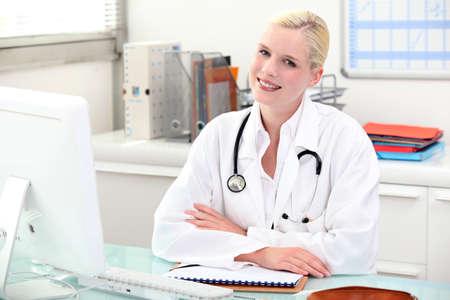 auscultation: Doctor sitting behind her desk